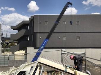屋根材を張る作業員