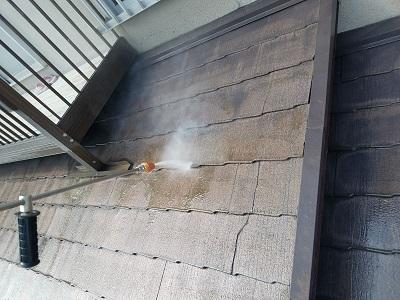 ひび割れたスレート屋根の塗装工事の水洗いの様子