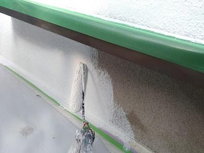 外壁に下塗り材を塗る様子