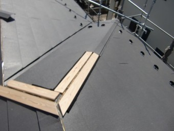 屋根の継ぎ目に垂木と棟板金を被せる様子