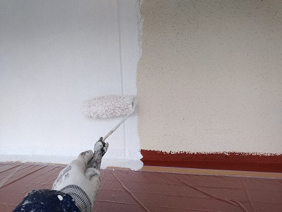 外壁に下塗り材を塗っていく様子