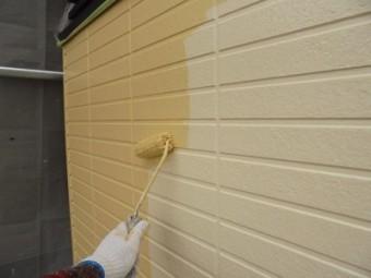 外壁に下塗り材塗装後、塗料本材を塗る様子