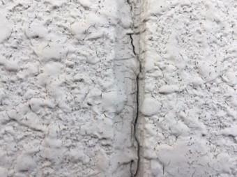 塗膜が割れてしまった外壁の現地調査の様子