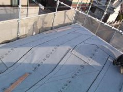 屋根に防水シートを貼っている様子