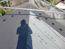 防水シートの上から金属の屋根材を被せていく様子