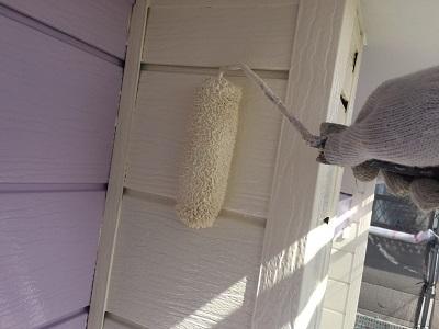 下塗りを終えた外壁材に塗料本材を塗布している様子
