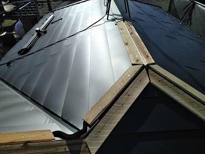 金属の屋根材を被せている途中の様子
