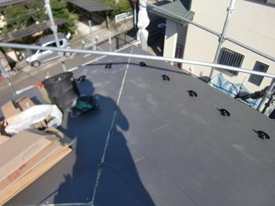 金属の屋根材を被せていく様子