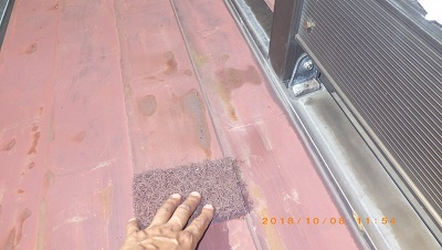 屋根の塗装工事の錆び掃除の様子