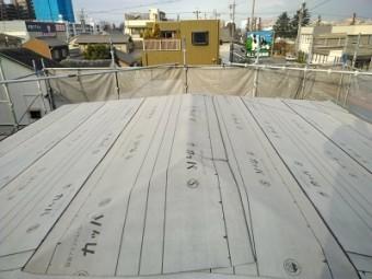 カラーベストの割れがある屋根の重ね葺き工事の防水シート施工中の様子