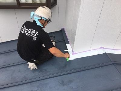 トタン屋根に錆止めを塗装する様子