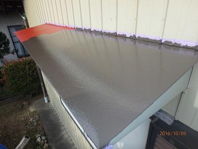 庇に塗料の上塗り剤を塗装する様子